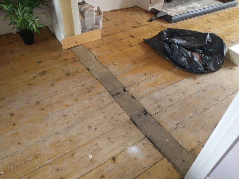 two wood floors with concrete brick transition